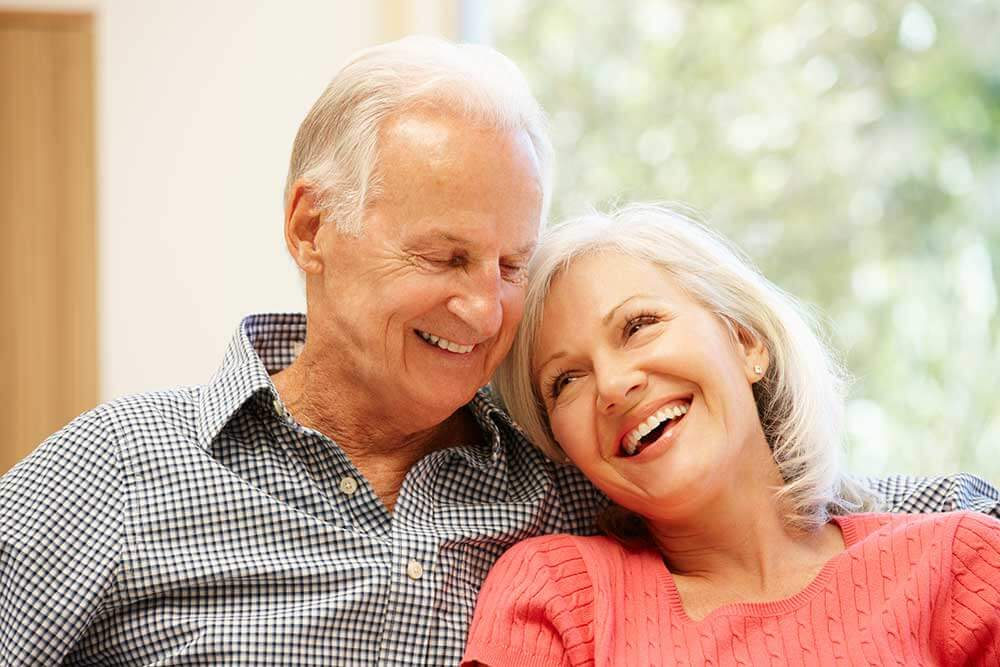 Older couple smiling and sitting close together