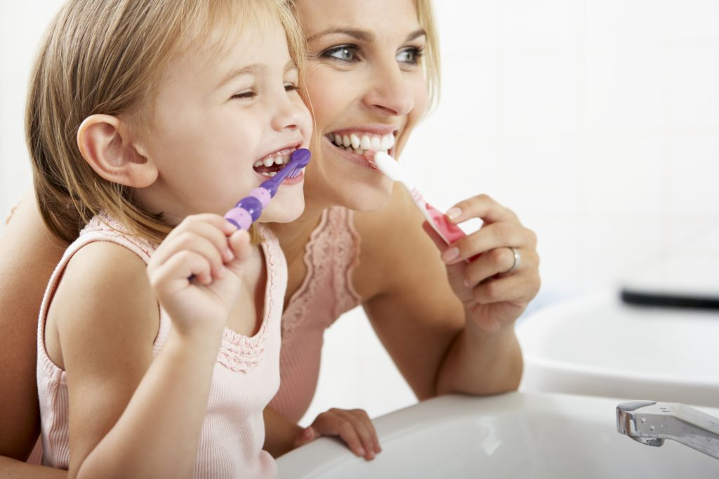 A mother and her young daughter brushing their teeth.