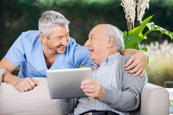 An older patient holding a tablet and sitting on the couch while a doctor stands over him with his arm around him