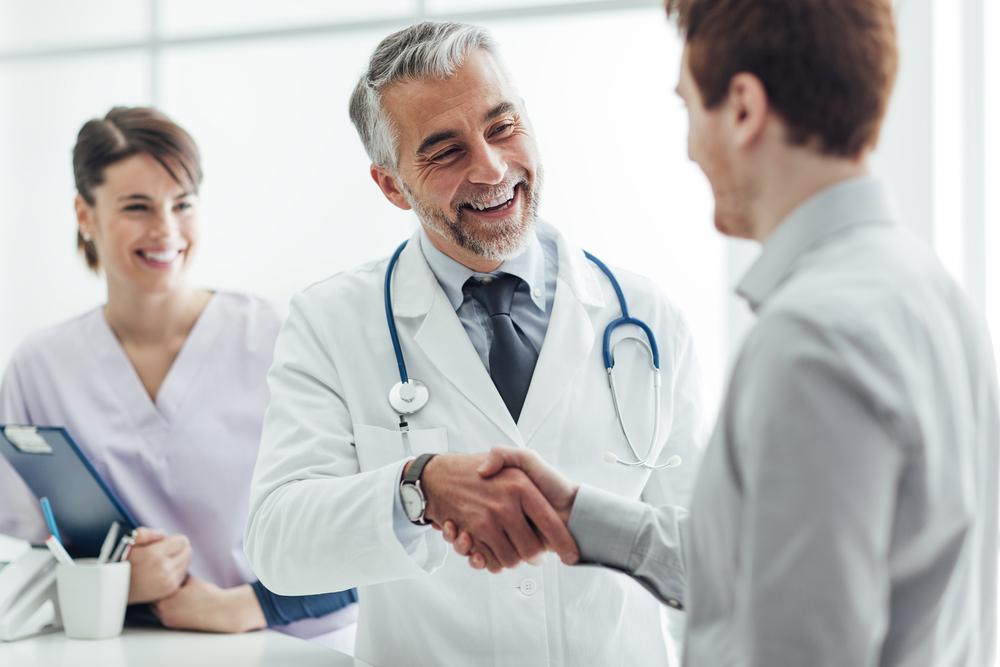 A doctor shaking hands with a patient and smiling