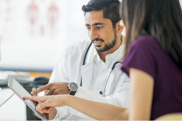 A doctor showing his patient something on the tablet